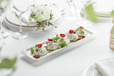 Fresh burata cheese with tomatoes and herbs on white plate Standard-Bild