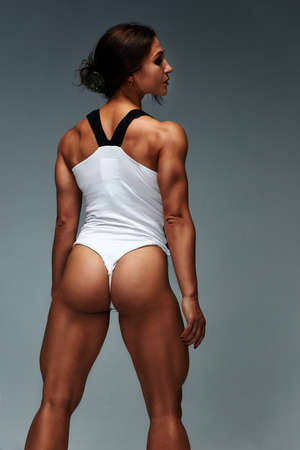 Girl with gorgeous muscular body in a white bathing suit on a gray background. Fitness. Muscular body.