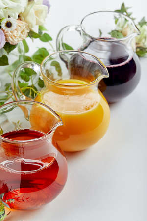 Jugs with different juices on event catering. Apple, orange, cherry and tomato juices Standard-Bild