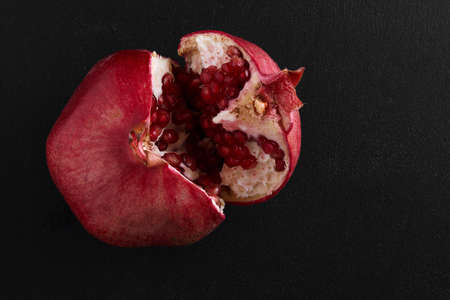 breaking pomegranate in half on black background Standard-Bild