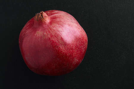 female hands breaking pomegranate in half on black background Standard-Bild