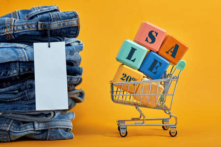 A stack of blue jeans with a white blank tag on a yellow background. Shopping trolley with multi-colored cubes. Sales word written on cubes. Sales consept