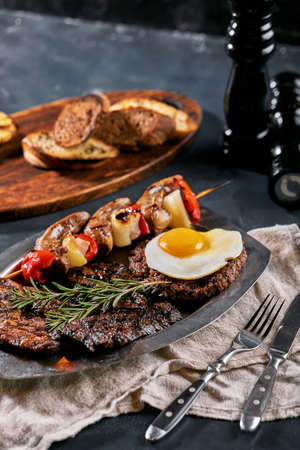 Grilled meat platter. Assorted delicious grilled meat with vegetables. Grilled mixed meat with pepper sauce and vegetables. Chefs hands spread meat on a plate Banco de Imagens