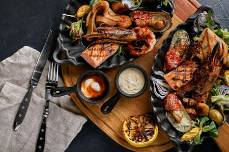 grilled seafood platter. Assorted delicious grilled seafood with vegetables. Grilled mixed bastards with pepper sauce and vegetables. Black background Banco de Imagens