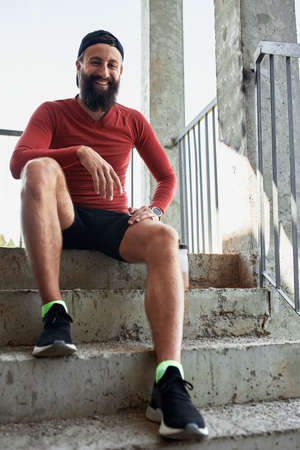 active smilling bearded sportsman having rest and sitting on stairs in bright day