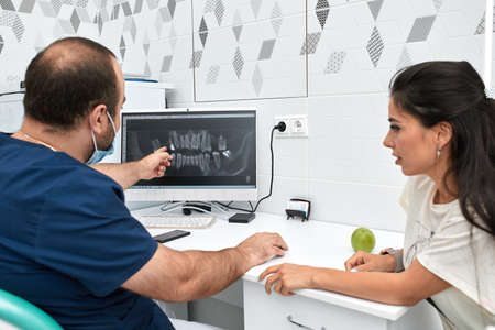 people, medicine, stomatology and health care concept - happy male dentist showing work plan to woman patient at dental clinic office Banco de Imagens