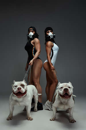two young sporty women in protective mask keep dog american bully on a leash dogs. Pandemic. Coronavirus concept. Health protection during covid-19 outbreak Reklamní fotografie