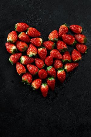 Fresh strawberries array heart shape on black background. Love concept. Valentines Day Concept. Winter Concept. Banco de Imagens