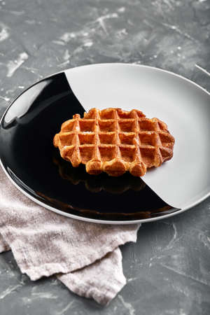 Belgian or american waffle, delicious sweet dish, dessert snack menu concept on black and white plate. top view. copy space for text Banco de Imagens