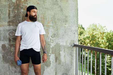 active smilling bearded sportsman having rest on stairs in bright day