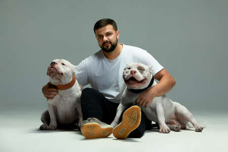 Handsome man and a charming dogs. Close-up, indoors. Studio photo, white color. Concept of care, education, obedience training and raising pets