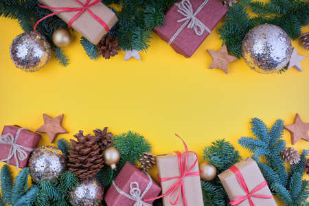 Spruce branch, cones and vintage toys decoration on christmas or new year on yellow background.