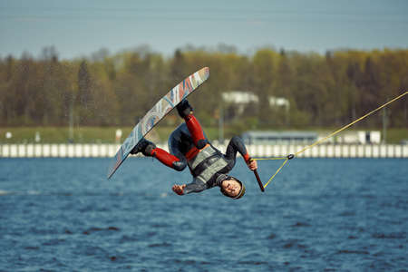 Young man riding wakeboard on a summer lake Banco de Imagens