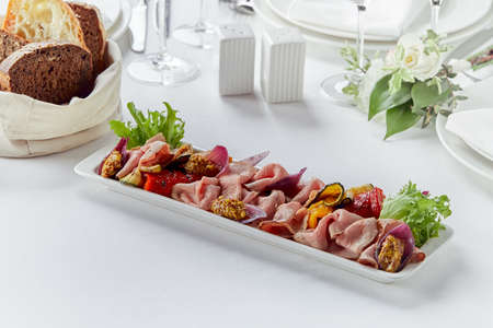 Sliced Beef or Pork with Marinated Vegetables and Sauce. Beautifully decorated catering banquet menu. Food snacks and appetizers for buffet on white background