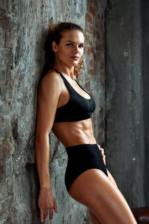 Portrait of athletic caucasian attractive fit woman dressed in top and leggins, against stone wall background. Sport, Fitness, Crossfit