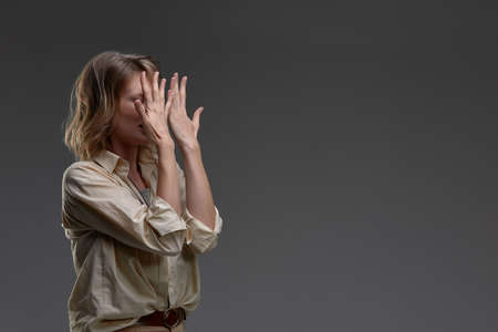 beautiful business woman covering her face with hands and crying, isolated on gray background