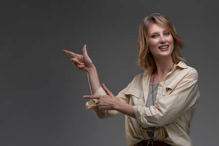 Beautiful smiling woman pointing with both hands to copyspace on her left hand side against a grey studio background