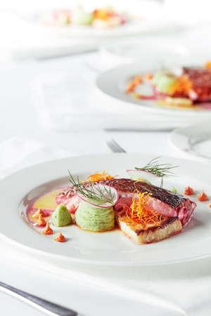 Tender dorado fillet with vegetables and basil. Banquet festive dishes. Gourmet restaurant menu. White background.