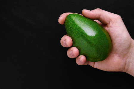 green fresh avocado in male hand over black background close-up