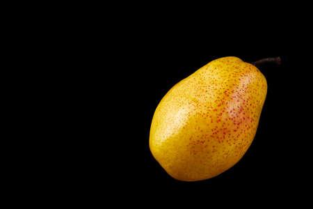 Beautiful ripe yellow pear on black background.