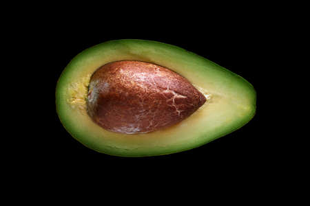 Macro shot of fresh avocados cut in a half on the black background