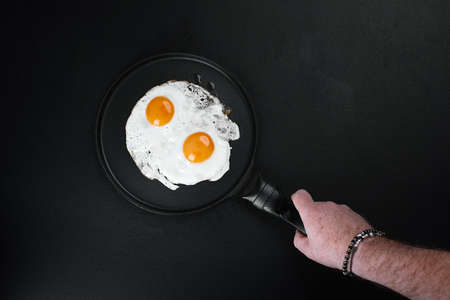 Fried Eggs In A Frying Pan in male hand on black background, copy space