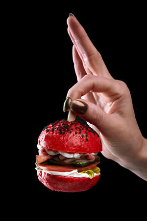 female hand holding mini burger as a Christmas tree toy on black background 스톡 콘텐츠
