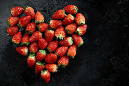Fresh strawberries array heart shape on black background. Love concept. Valentines Day Concept. Winter Concept. 스톡 콘텐츠