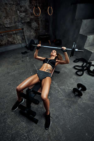 a girl with dumbbells is engaged in bodybuilding on the background of the gym , a woman is engaged in fitness with dumbbells in the fitness room
