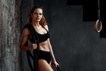 Battle ropes session. Attractive young fit and toned sportswoman working out in fitness training gym