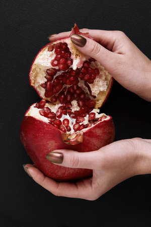 female hands breaking pomegranate in half on black background 스톡 콘텐츠