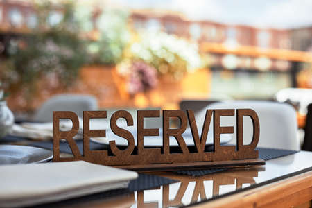 Reserved table sign in a restaurant on summer terrace