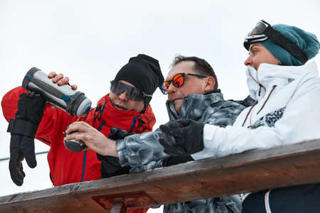group of skiers friends on the mountain are resting and drinking coffee
