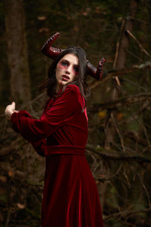 Stylish and fashionable model girl in the image of posing among mystic forest - fairytale story, cosplay. Halloween