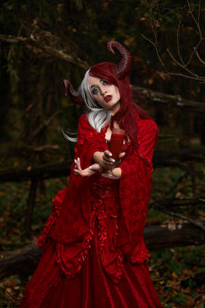 Stylish and fashionable model girl in the image of Maleficent posing among mystic forest - fairytale story, cosplay. Halloween Stockfoto