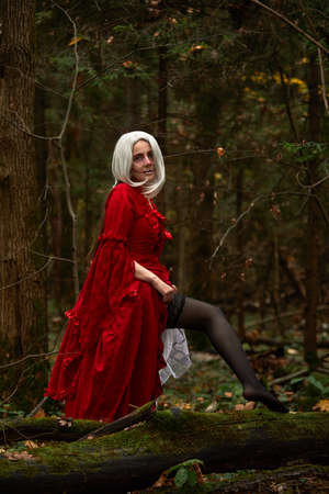 Halloween concept, glamorous costume detail. Young beautiful and mysterious woman in woods, in white Dress and Red Cloak. Little red hood or vampire story Фото со стока