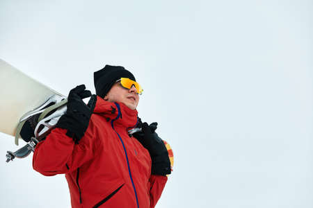 Male snowboarder in a red suit walking on the snowy hill with snowboard, Skiing and snowboarding concept