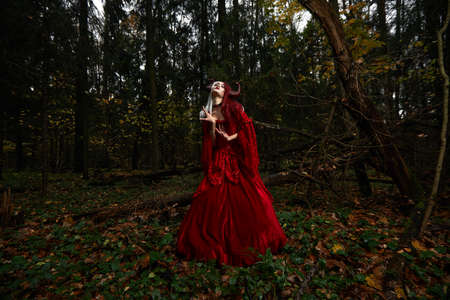 Stylish and fashionable model girl in the image of Maleficent posing among mystic forest - fairytale story, cosplay. Halloween