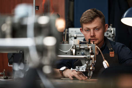 Working process of leather craftsman. Tanner or skinner sews leather on a special sewing machine, close up.worker sewing on the sewing machine Stock Photo