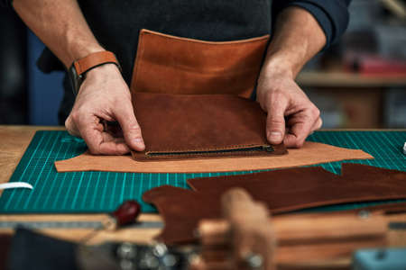 Skilled leather manufacture worker cutting some samples