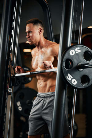 Closeup portrait of a muscular man workout with barbell at gym. Brutal bodybuilder athletic man with six pack, perfect abs, shoulders, biceps, triceps and chest