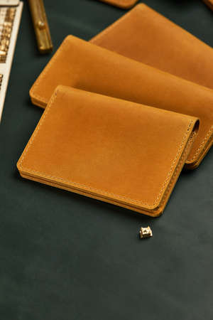 Handmade products made of genuine yellow and red leather. Leather passport cover, leather wallet. Leather goods for men. The view from the top Imagens