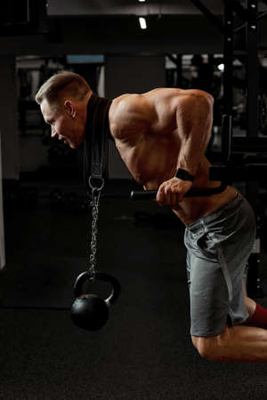 Powerful bodybuilder doing the exercises with dumbbells. Photo of strong male with torso on dark background. Strength and motivation.