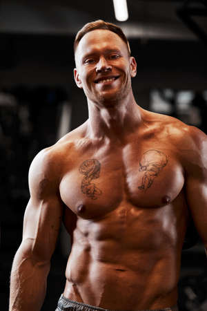 Powerful bodybuilder doing the exercises with dumbbells. Photo of strong male with naked torso on dark background. Strength and motivation. Imagens