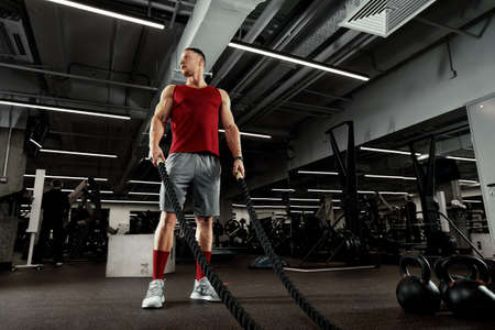 Sport. Strong man exercising with battle ropes at the gym with. Athlete doing battle rope workout at gym. Dramatic sports background. Imagens