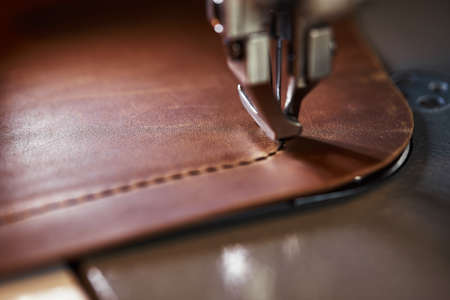 Working process of leather craftsman. Tanner or skinner sews leather on a special sewing machine, close up.worker sewing on the sewing machine Imagens - 167914454