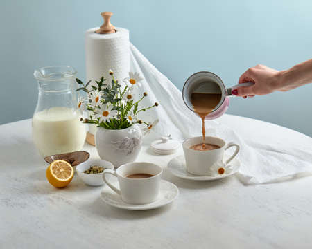 Breakfast is served on a table with light blue background. Breakfast setting over blue table with copy space border. Coffe with milk. Flat lay