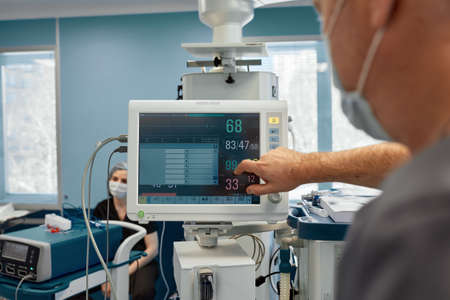 Anesthesiologist keeping track of vital functions of the body during cardiac surgery. Surgeon looking at medical monitor during surgery. Doctor checking monitor for patient health status.