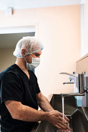Male surgeon washing his hands at the hospital. Healthcare workers in the Coronavirus Covid19 pandemic