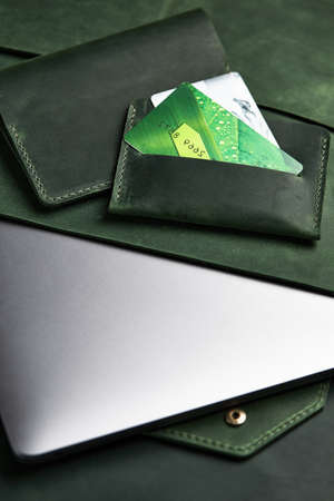 green wallet and genuine leather laptop case and cardholder lie on table Imagens